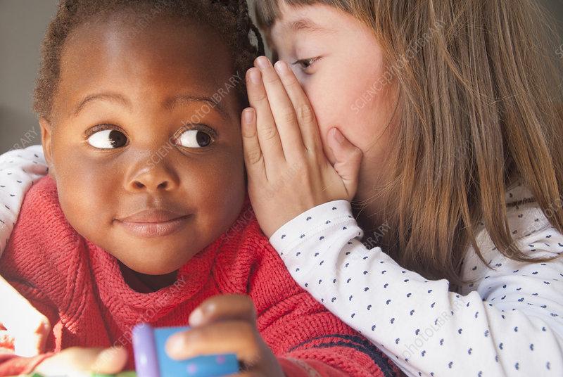Girl whispering to female toddler