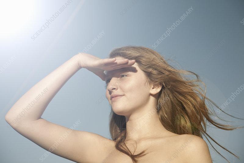 Teenage girl shielding her eyes