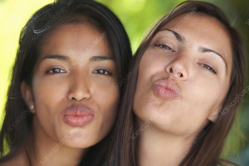 Two woman friends puckering lips