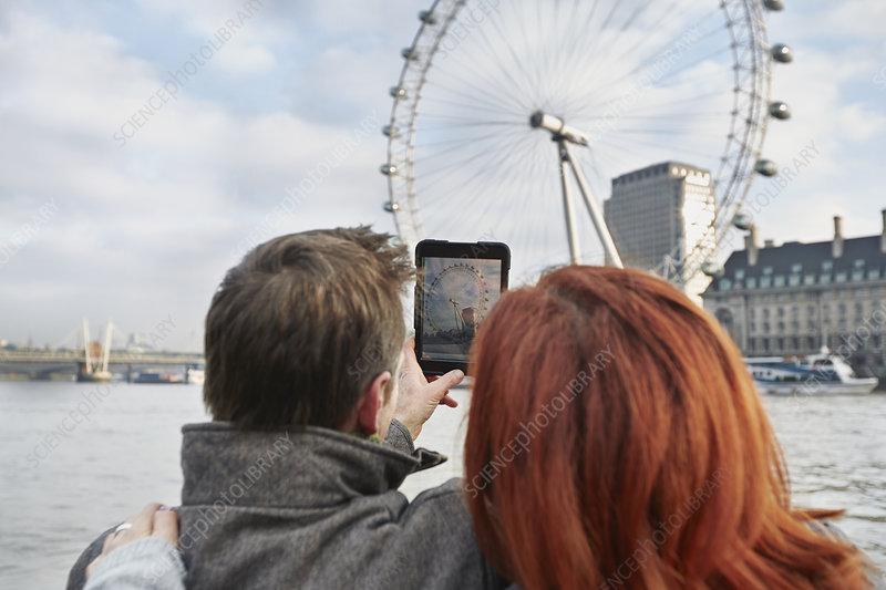 Tourists photographing London Eye, UK