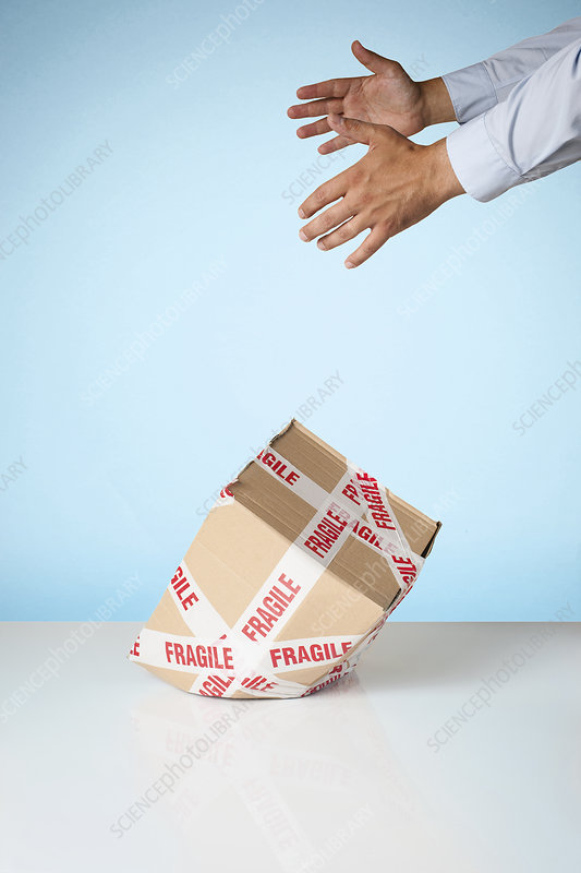 Hands dropping cardboard box
