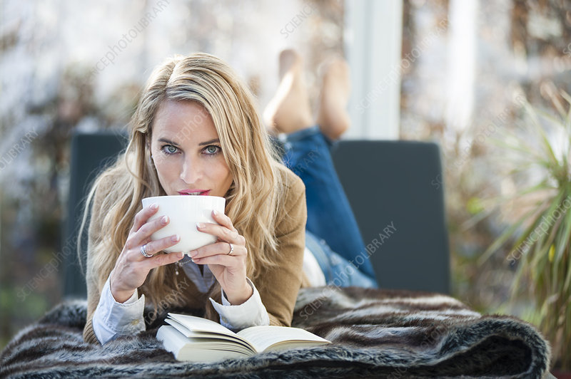 Woman relaxing on sofa drinking coffee