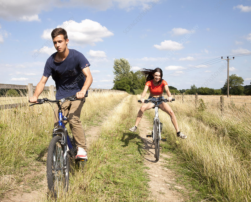 Young couple cycling through field