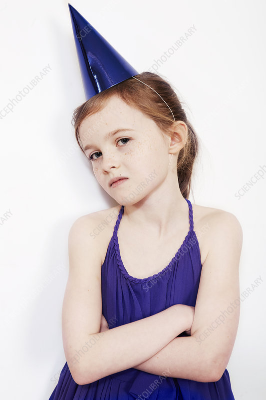 Girl wearing party hat with arms folded
