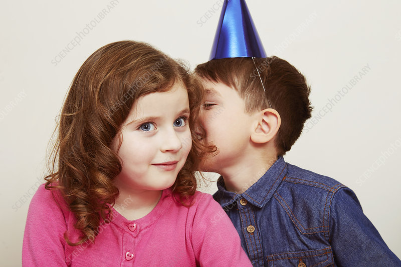 Boy wearing party hat whispering to girl