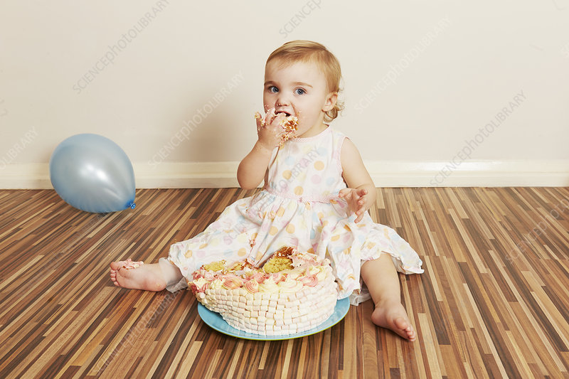 Toddler girl devouring birthday cake