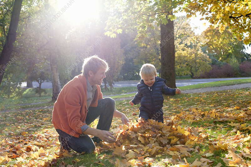 Father and son playing with autumn leaves