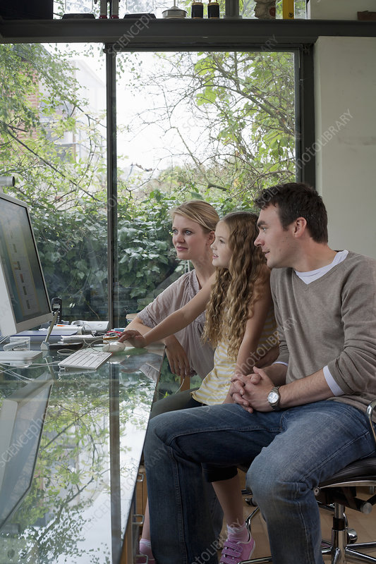 Girl and parents at home using computer