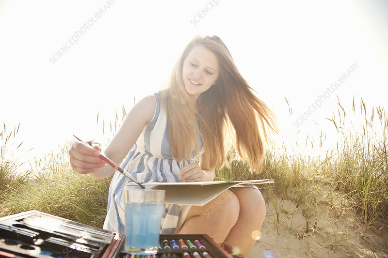 Teenage girl drawing on the beach