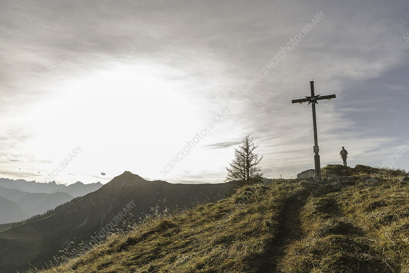 Silhouette of woman and wooden cross