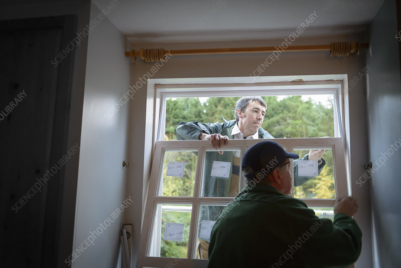 Builders installing new window in house