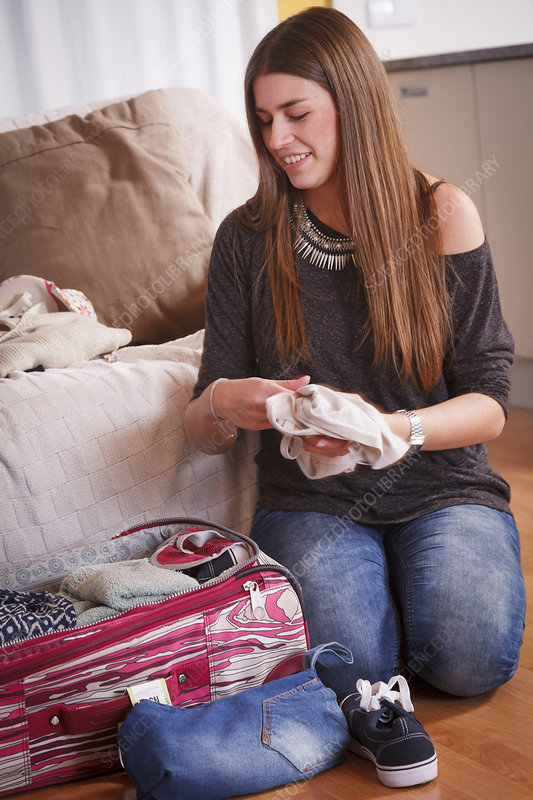 Young woman packing luggage