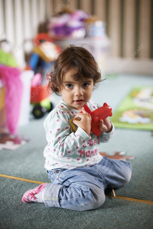 Toddler playing with a red toy