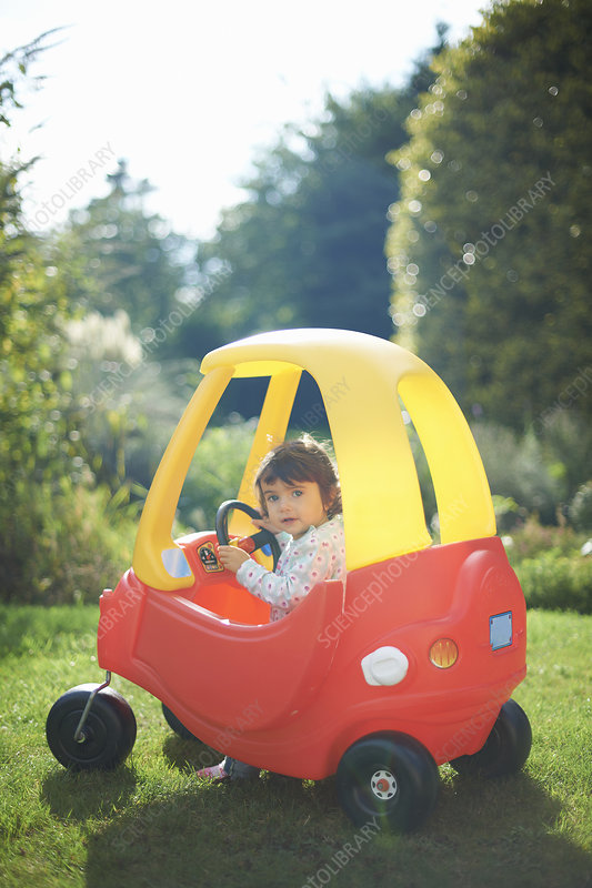 Toddler playing in toy car in the garden