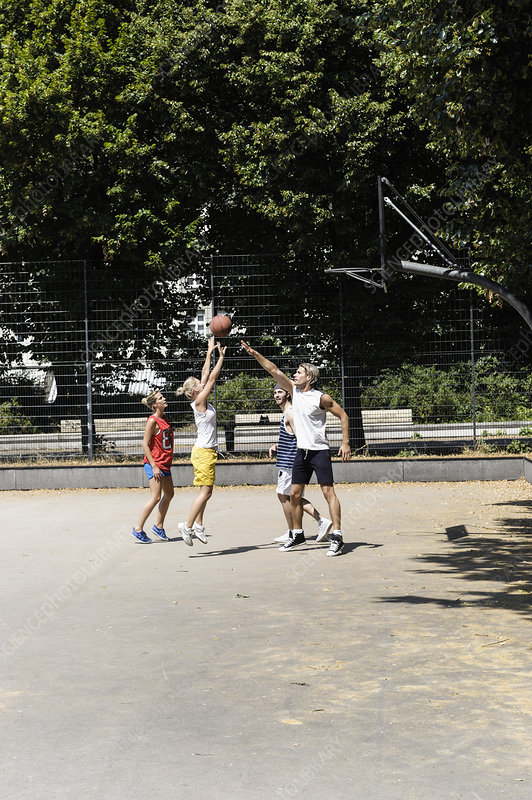 Friends playing basketball on court