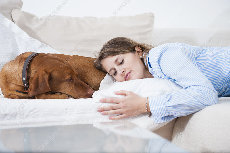 Young woman asleep with her dog on sofa