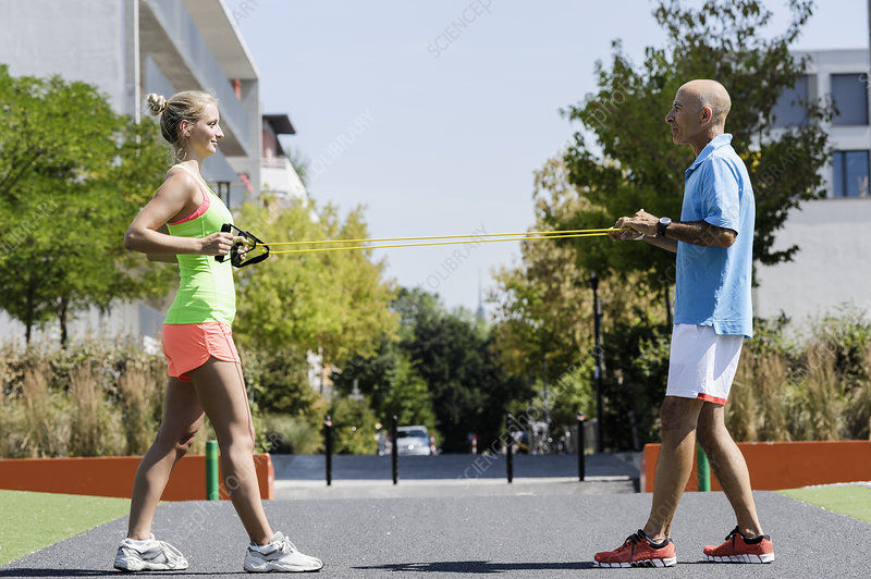 Woman and trainer using exercise ropes
