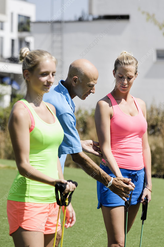Two women and trainer with exercise ropes
