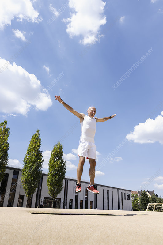 Mature man doing jump exercise in park