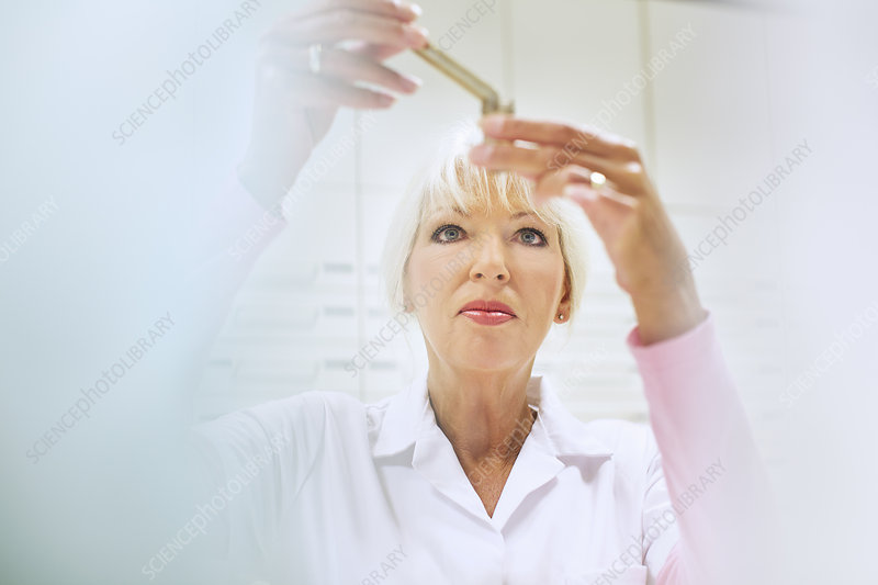 Pharmacist measuring medicines