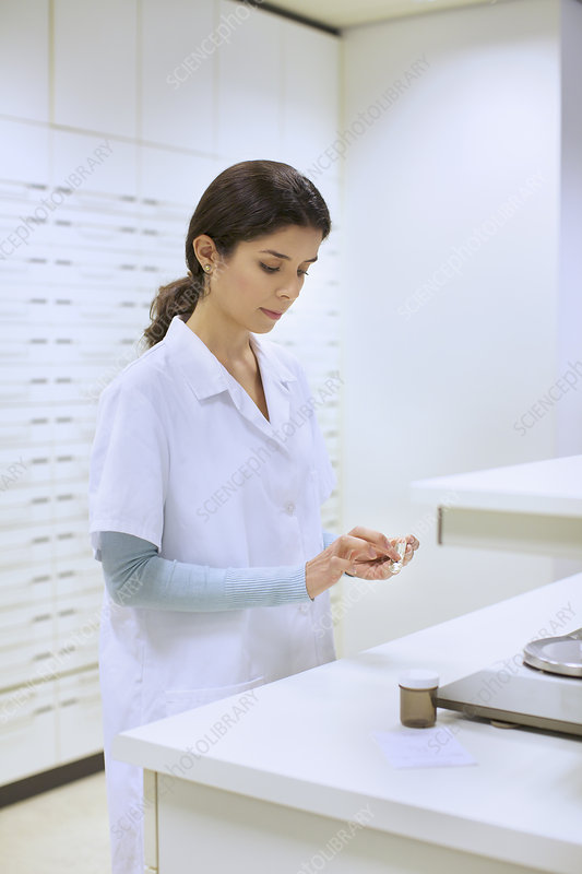 Pharmacist weighing medicines