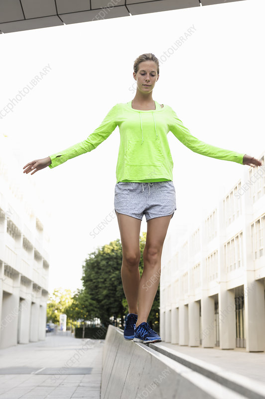 Young woman walking on divider