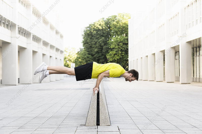 Man balancing horizontally on divider