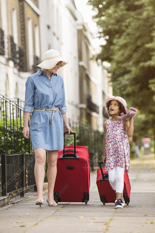 Mother and daughter with suitcases