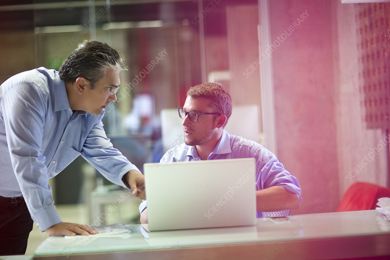 Businessman advising male office worker