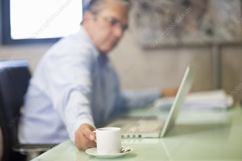 Mature businessman taking a coffee break