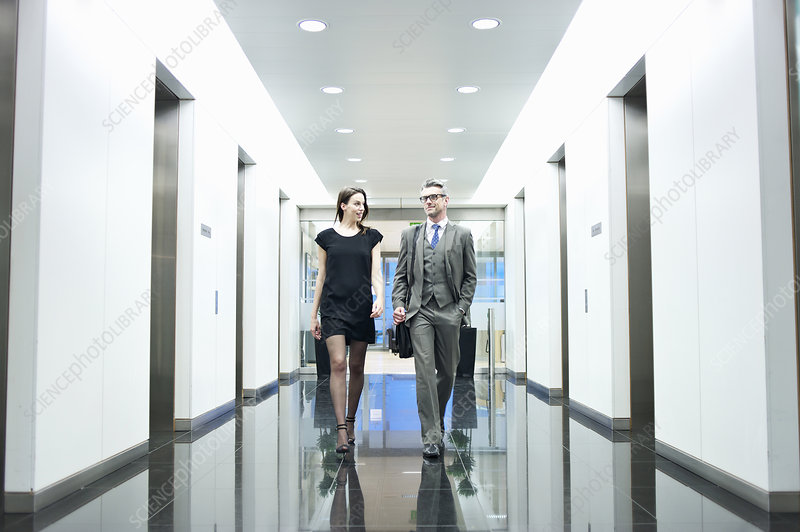 Business partners walking along corridor