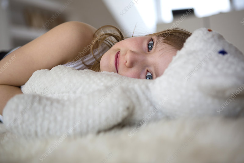 Girl lying on furry bed with teddy bear