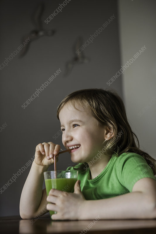 Girl drinking a glass of vegetable juice