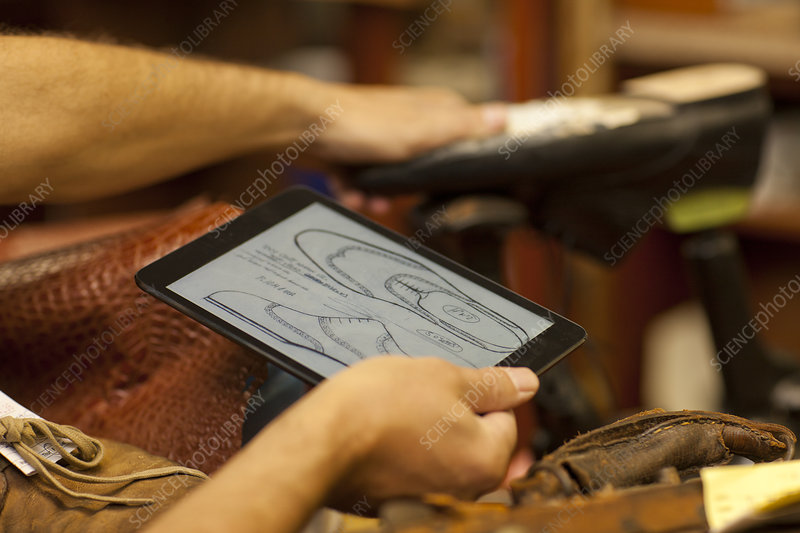 Cobbler holding digital tablet