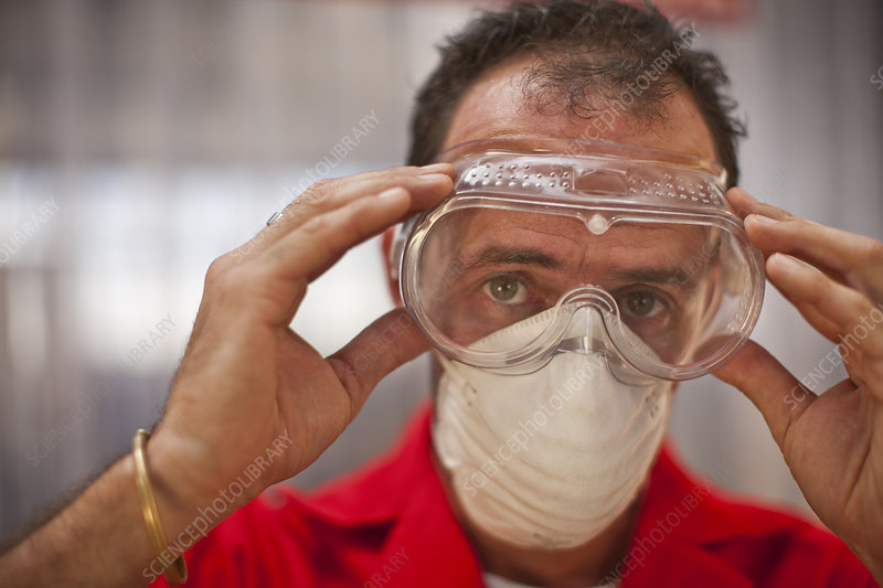 Carpenter putting on protective glasses