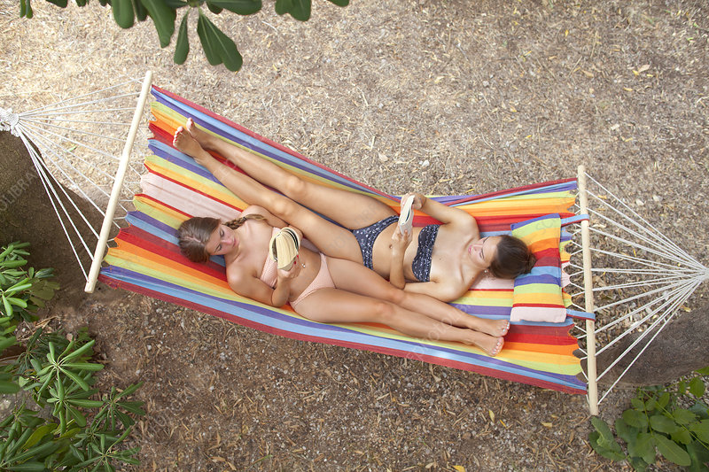 Young women lying on hammock reading