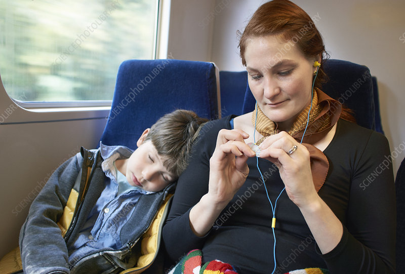 Mother and son sitting on train