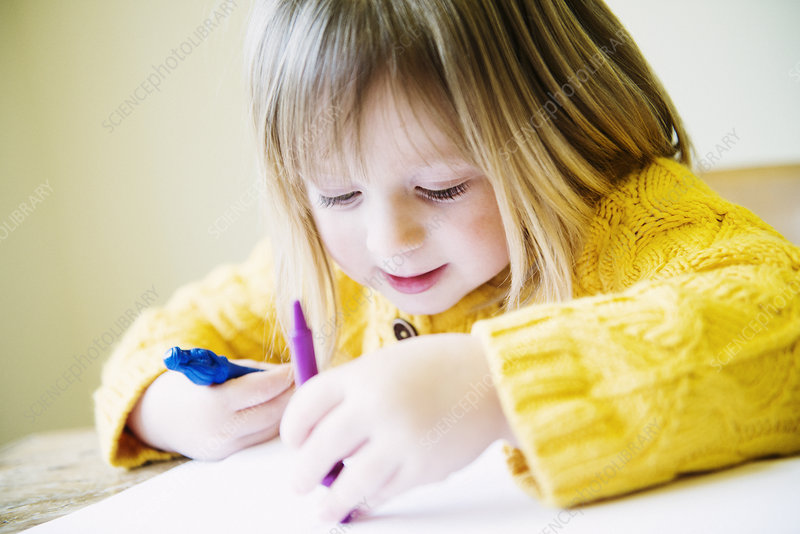 Young girl colouring in with felt pens