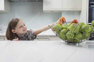 Young girl reaching for a tangerine