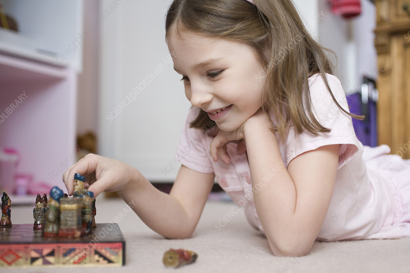 Young girl playing with chess set