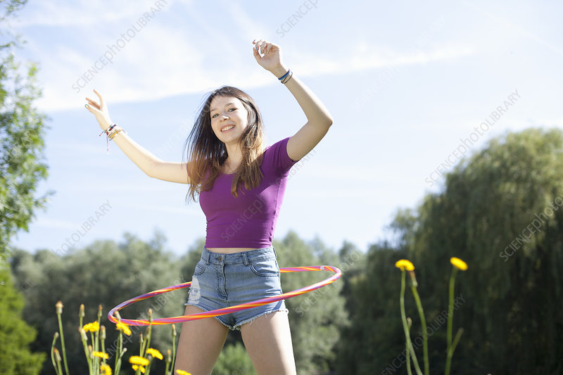 Teenage girl hoola hooping in park