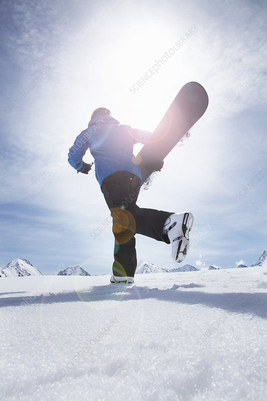 Mature man carrying his snowboard uphill