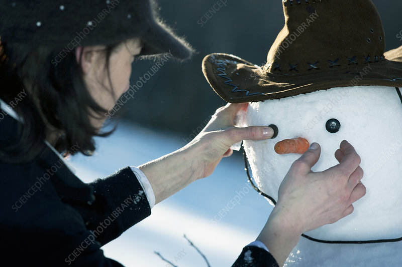 Woman placing the eyes on a snowman face