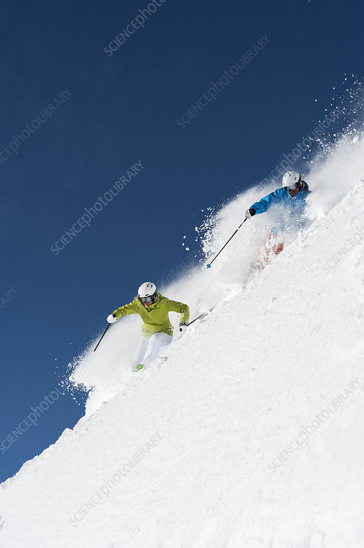 Male and female skiers racing downhill
