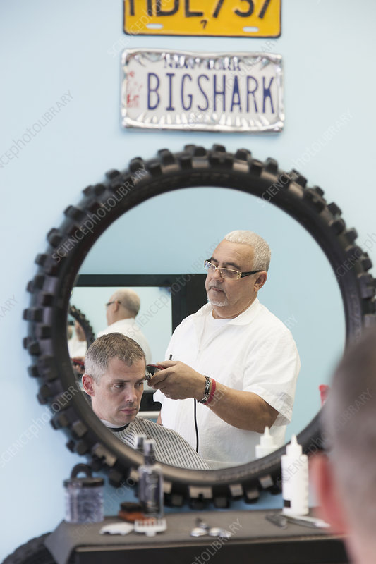 Barber shaving man's hair