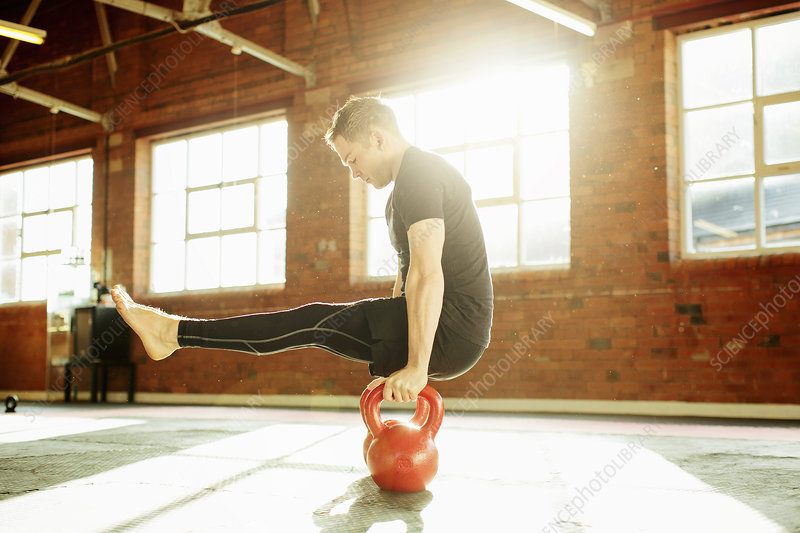 Man strength training with kettle bells