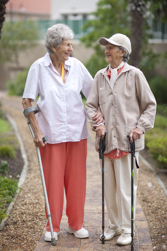 Two senior women strolling in garden