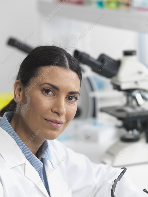 Researcher next to microscopes