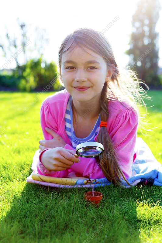 Girl with a magnifying glass and seedling