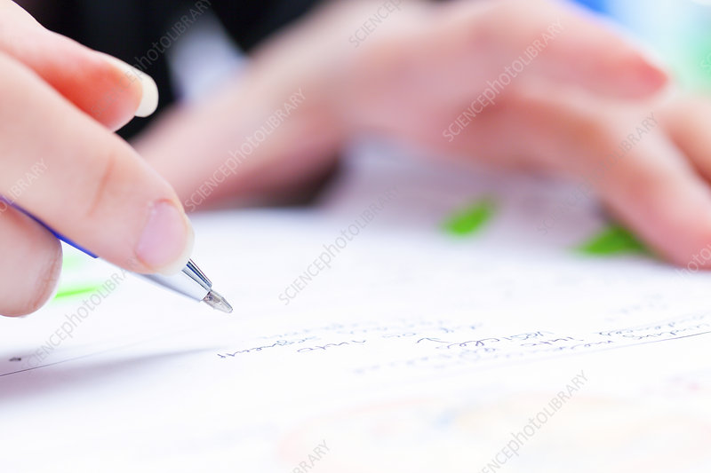 Person using a pen to sign a document